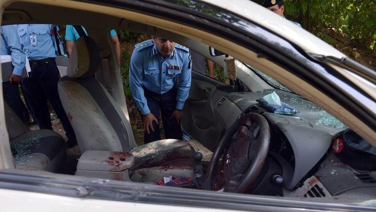 Agenten onderzoeken de met kogels doorzeefde auto van Chaudhry Zulfiqar Ali. Beeld afp