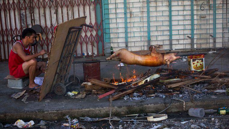 Een Filipino roostert varken op straat in de zwaar verwoeste stad Tacloban. Beeld AP
