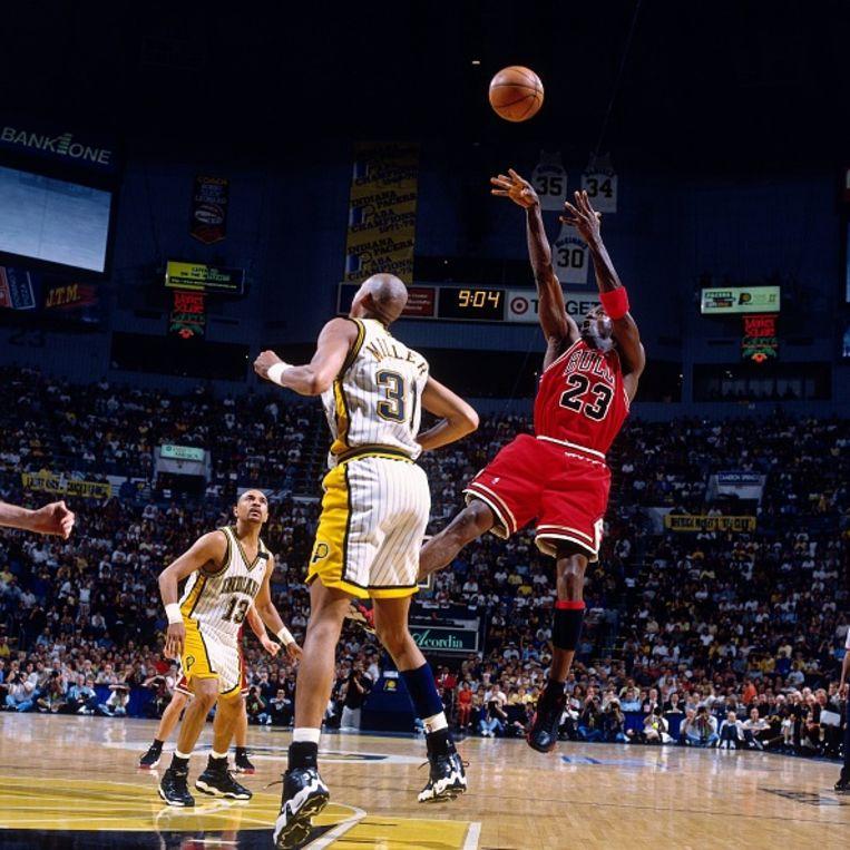 Michael Jordan hangt in de lucht voor zijn specialiteit, de zogeheten fadeaway. Bij die schotpoging stapt en springt hij achterwaarts, waarna hij de bal afvuurt.  Reggie Miller van de Indiana Pacers kijkt toe tijdens het duel in 1998. Beeld Getty Images