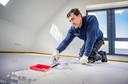 Danny Hartung van gietvloerenbedrijf DHT/Indigo Floor bezig met een cementgebonden gietvloer van 130 vierkante meter in een woning in Beemte Broekland.