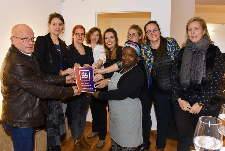 De ondernemers achter 7Stories nemen de prijs in ontvangst van schepen Luc Hermans.