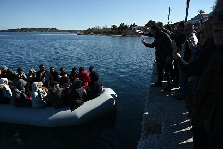 Migranten op een boot bij Lesbos. Beeld Aris Messinis / AFP