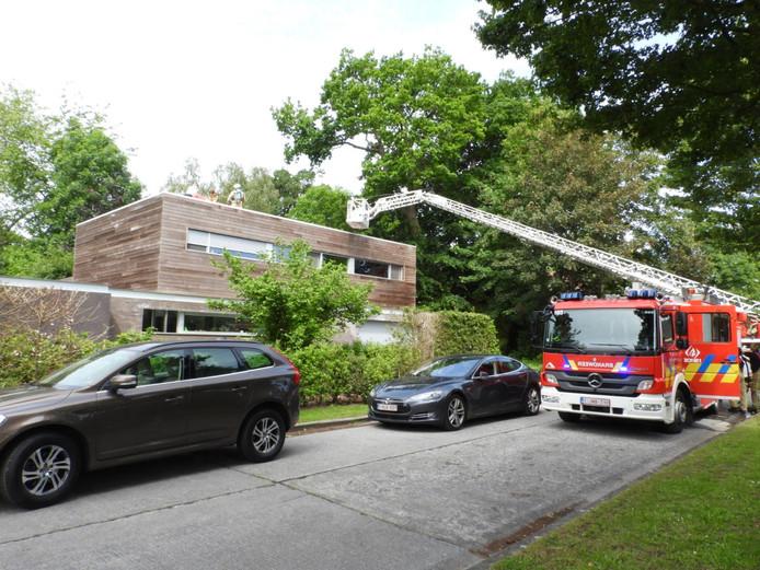 De brandweer op het dak van de woning.
