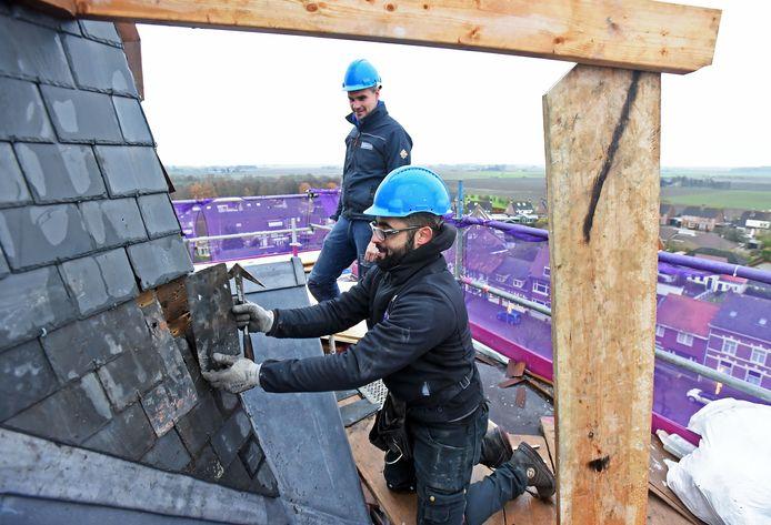 Dakbekleder Hicham legt nieuwe leitjes op de toren van de kerk in Zaamslag. Peter Doens kijkt toe.