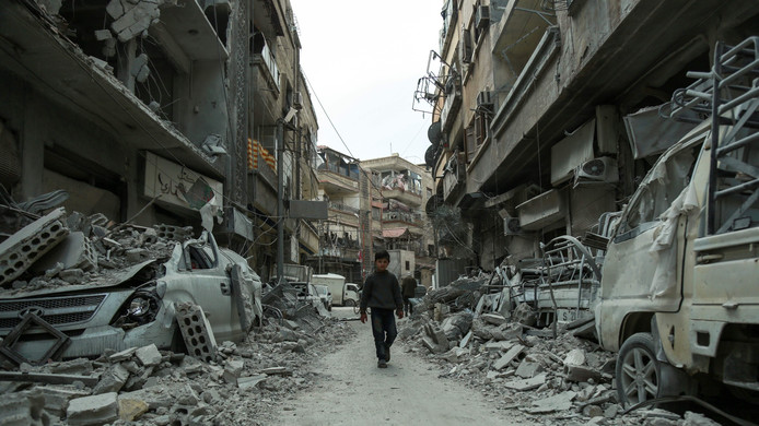Een Syrisch kind dat door de bende van een straat in Oost-Ghouta loopt.