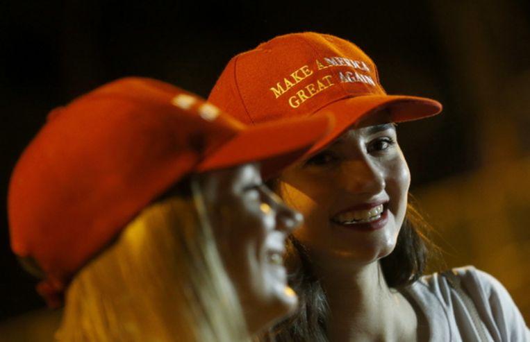 Twee vrouwen met 'Make America Great Again'-petjes wachten op de aankomst van President Donald Trump (Singapore). Beeld ANP