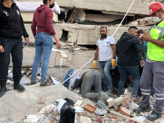 Des sauveteurs aidés par des volontaires fouillent les débris après l'effondrement d'un immeuble à Izmir.