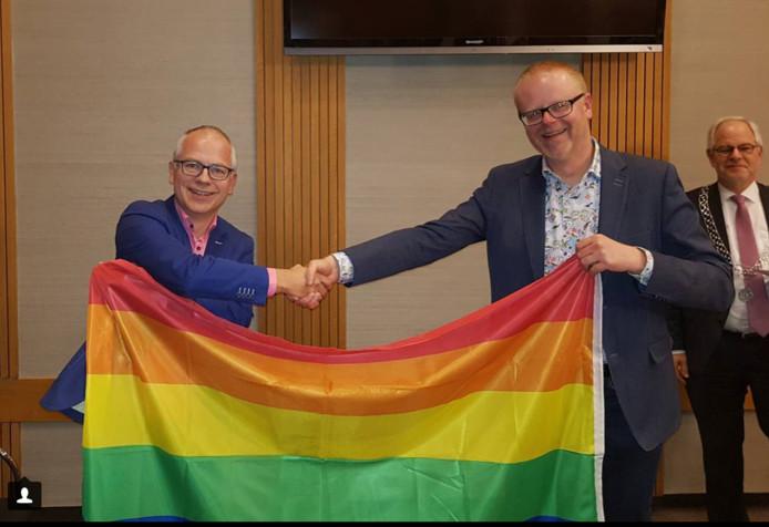 Sandor Löwik, fractievoorzitter van GroenLinks, krijgt een exemplaar van de regenboogvlag overhandigd door wethouder Rob Christenhusz (rechts).
