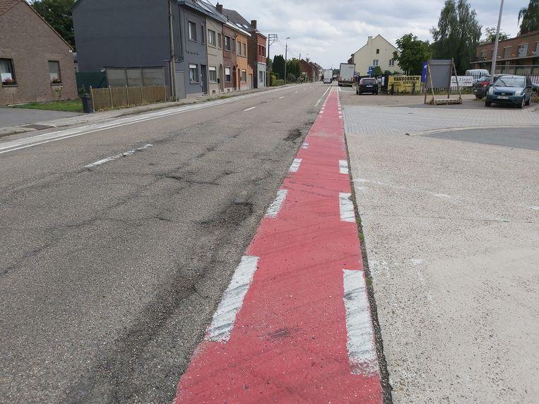 De weg en het fietspad bevinden zich in slechte toestand. In de achtergrond de betwiste parking voor camions