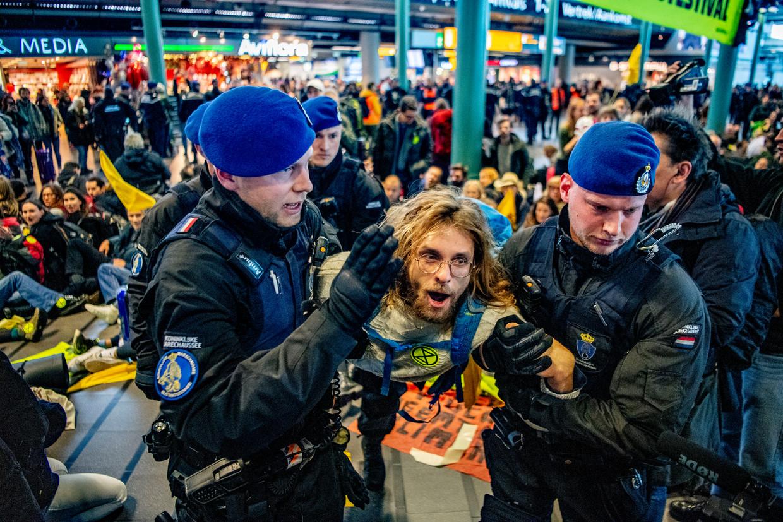 Actievoerders van Greenpeace worden verwijderd uit Schiphol Plaza. Beeld ANP