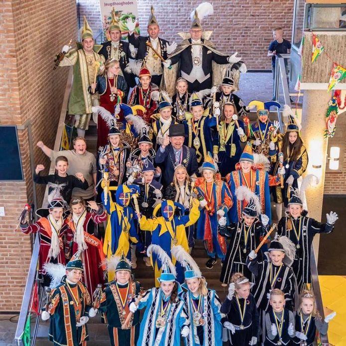 Burgemeester Patrick Welman in het centrum van van een schare carnaval vierende kinderen.