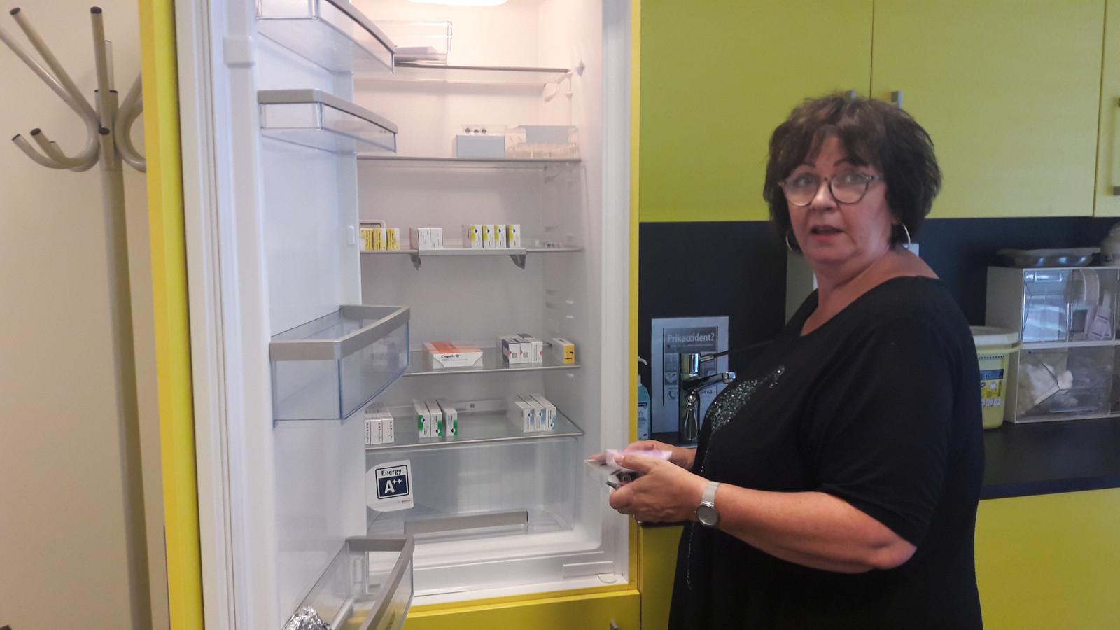 Verpleegkundige Annemarie Rouw-Zuidema van de GGD in Eindhoven bereidt de reisvaccinaties voor bij de koelkas in haar spreekkamer.