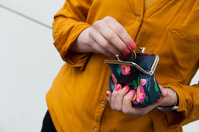 Een jonge vrouw pakt geld uit haar portemonnee.