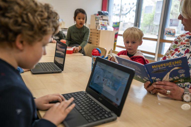 Kinderen aan het werk op  een naschoolse opvang voor kinderen van ouders met een vitaal beroep . Beeld ANP