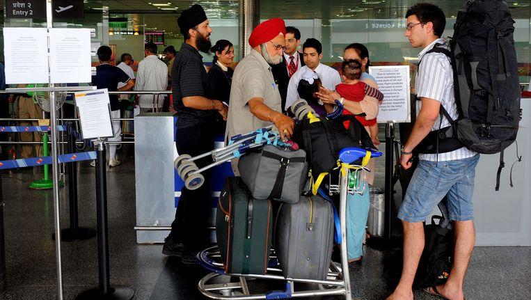 Passagiers op het vliegveld van New Delhi.