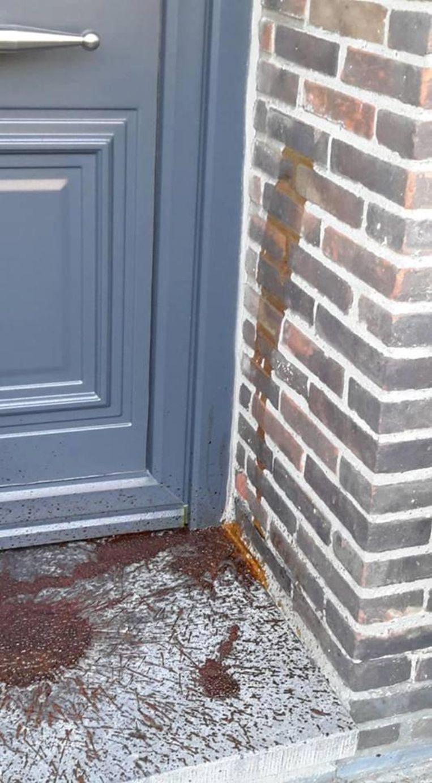 De roodachtige vloeistof bij een voordeur.