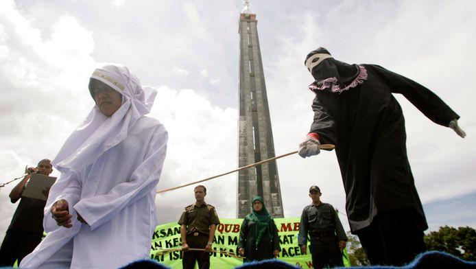 Archiefbeeld 2010: Een vrouw in Aceh krijgt publiek stokslagen omdat zij voedsel verkocht tijdens de Ramadan. Het slachtoffer van de groepsverkrachting hangt hetzelfde lot boven het hoofd.