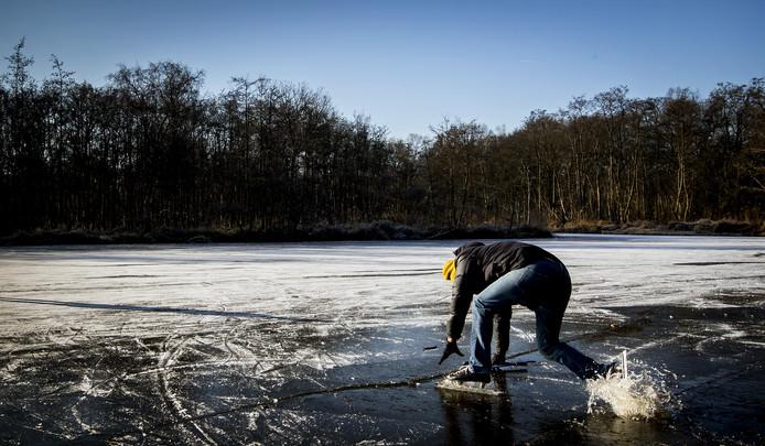 Een schaatser zakt door het ijs