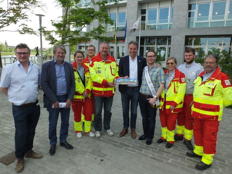 De vrijwilligers van Rode Kruis Deinze verkopen de eerste stickers aan leden van het stadsbestuur en aan Prins Canteclaer Amaury Wullaert.