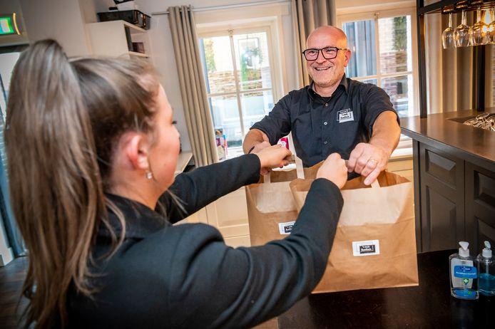 Fred Schel van brasserie 't Oude Raadhuis in Heesch geeft een klant twee tassen met eten mee.