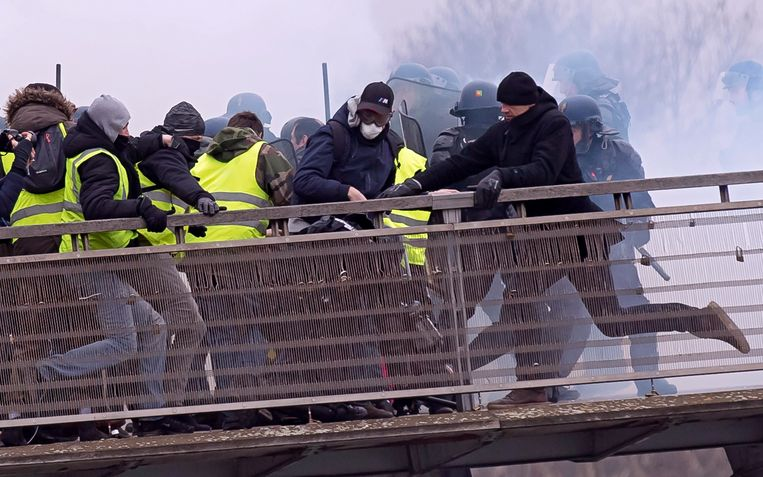 Chistophe Dettinger (rechts) trapt in Parijs in op een politieagent die op de grond ligt.