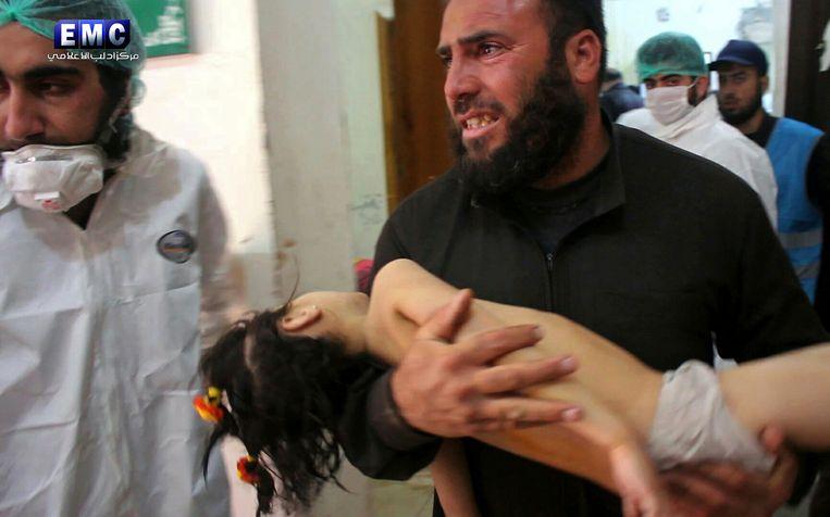 Een man draagt een slachtoffer van de aanval op Khan Sheikhoun dinsdag. Beeld AP