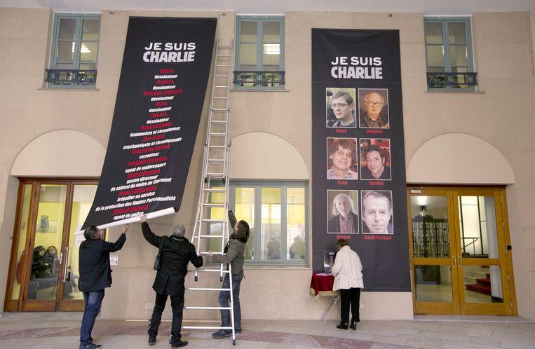 Een banier wordt opgehangen met namen en foto's van de slachtoffers, waaronder Maris. Beeld afp