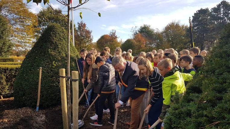 De leerlingen planten samen met Luc Aerts de vredesboom.