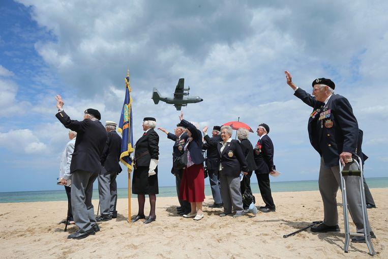 Veteranen van de Royal Wootton Bassett Normandy Veterans Association zwaaien naar een vliegtuig dat tijdens de herdenkingsbijeenkomst over Sword Beach vliegt. Beeld getty