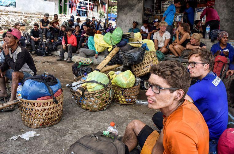 Indonesische en buitenlandse wandelaars die na de aardbeving van gisteren van de berg Rinjani zijn weten te komen, worden opgevangen in Sembalun op het eiland Lombok. Beeld null