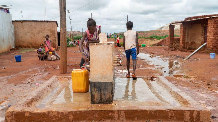 De waterpomp in het centrum van de wijk Ruashi, met daarachter de diepe mijn van Ruashi Mining. Beeld Sarah Haaij