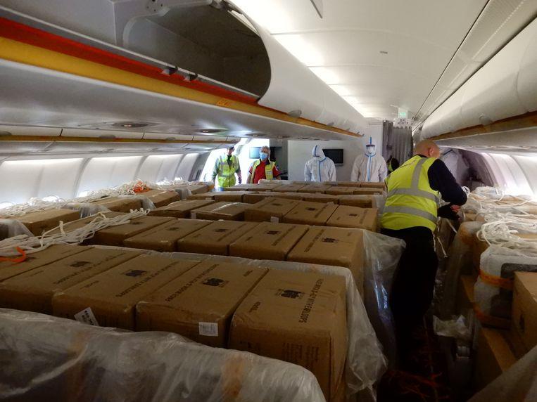 De passagiersruimte is volgestouwd met dozen met mondmaskers.