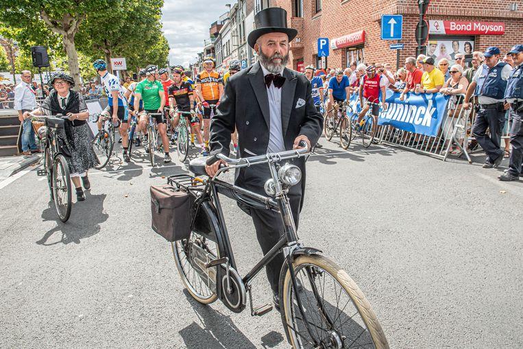 Strak in het pak en met een fiets uit vervlogen tijden.
