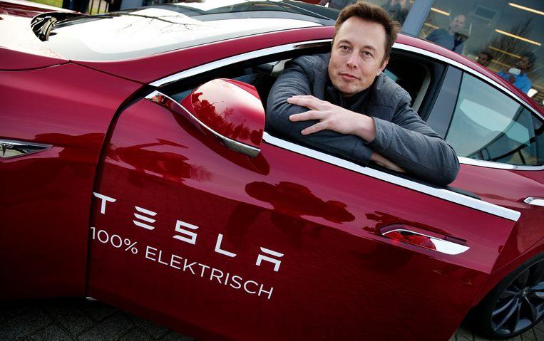 Elon Musk, CEO van Tesla, poseert bij een model van zijn merk tijdens zijn bezoek aan Nederland in 2014. Beeld ANP
