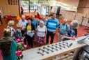 Gemeenschap van Moeder Theresakerk zes weken na de brand bijeen in Esreinschool na de dienst even na praten.