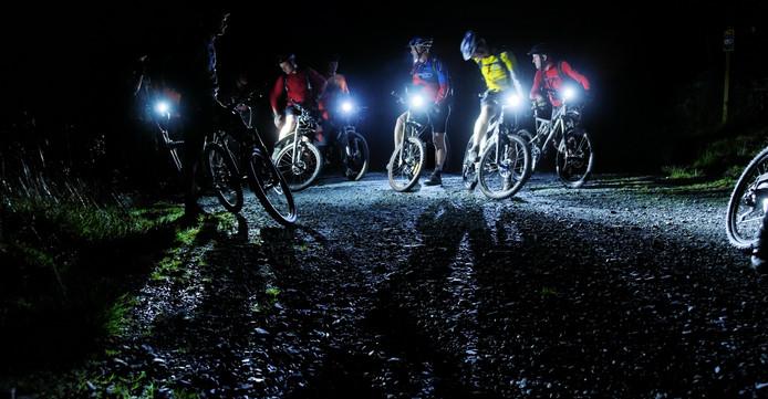 Een groep mountainbikers overlegt in een donker bos.