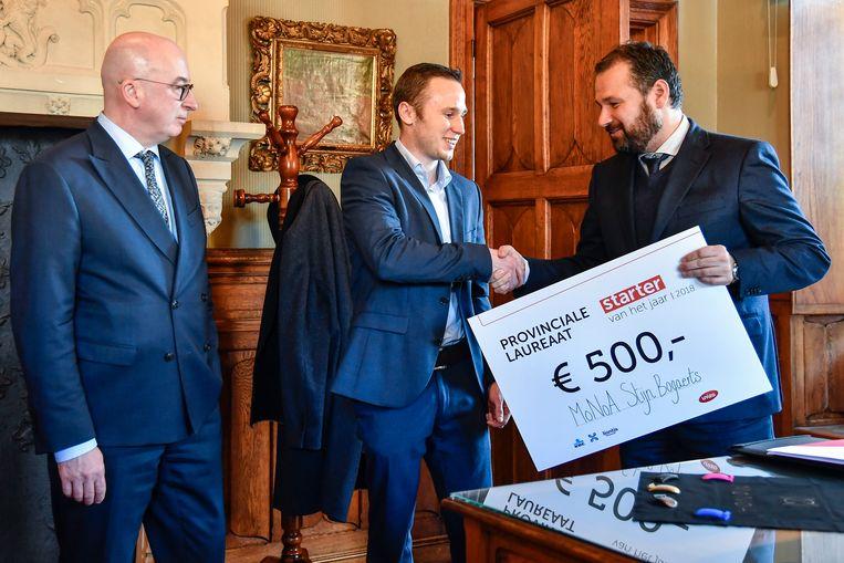 """De titel van Oost-Vlaamse """"Starter van het Jaar"""" levert Stijn Bogaerts 500 euro. Unizo-directeur Jos Vermeiren overhandigde de cheque in het Dendermondse stadhuis, in het bijzijn van burgemeester Piet Buyse."""