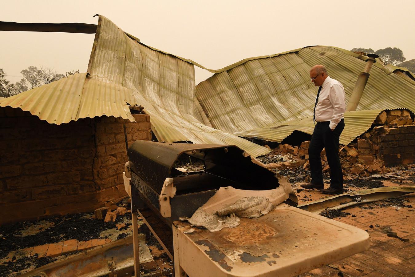 De Australische premier Scott Morrison bekijkt de schade bij een boerderij in Sarsfield, Victoria.