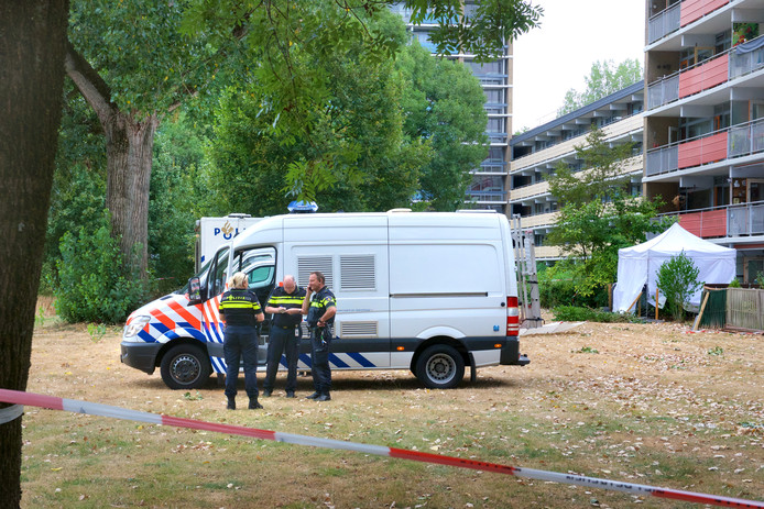 Politie-onderzoek met op de achtergrond de tuin van het slachtoffer.
