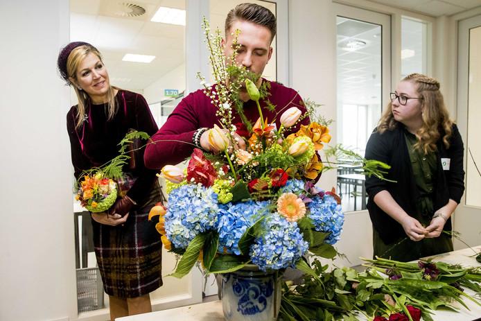 Koningin Maxima kijkt hoe een bloemist een boeket maakt tijdens een rondleiding door het internationale kennis- en innovatiecentrum voor de glastuinbouw in het Westland. Foto:Patrick van Katwijk