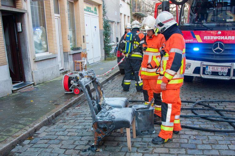 Brandweermannen bij de verbrande stoelen.