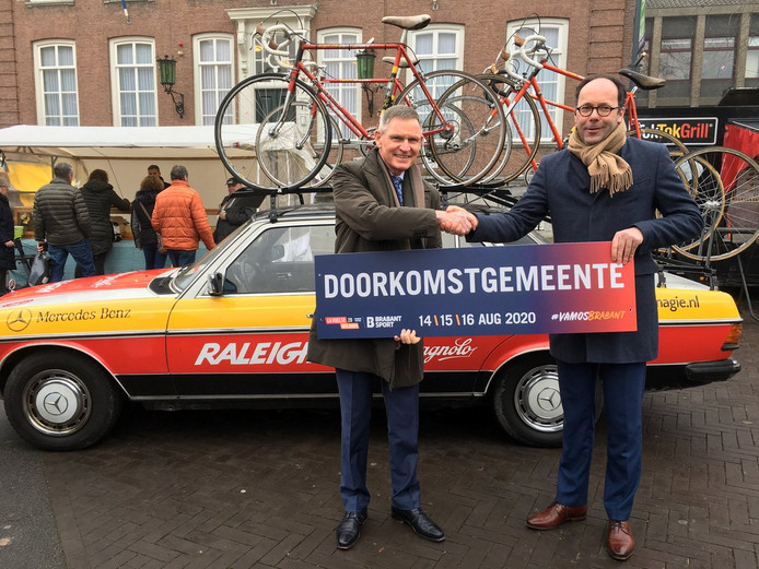 Wethouder Peter van der Ven van Altena (links) krijgt uit handen van de gedeputeerde een doorkomstbord. De Vuelta-renners komen onder meer door Wijk en Aalburg, Andel en Giessen