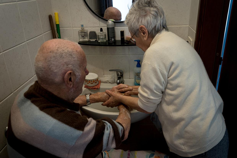 Ines (85) wast de handen van Gino (87), uit de fotoserie van Marzio Toniolo. Beeld Marzio Toniolo/Reuters