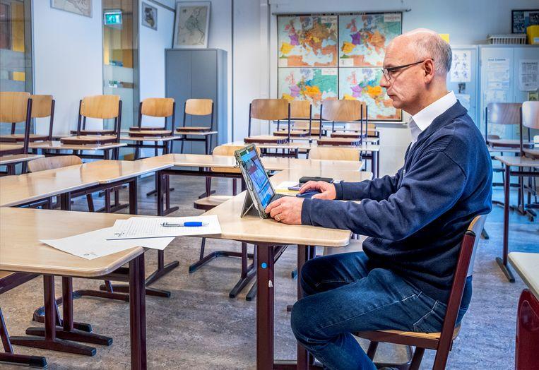 Han Fortmann-docent Peter van der Linden geeft les vanuit een leeg klaslokaal. Beeld Raymond Rutting / de Volkskrant