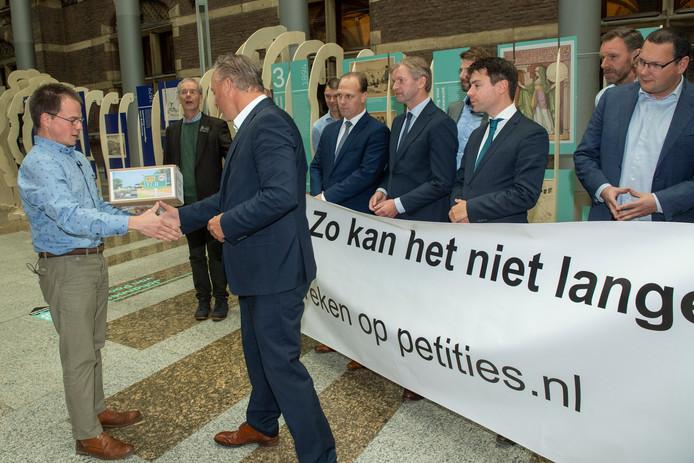 Namens de Sallandse dorpen langs de N35 overhandigt Niels Tomson de petitie 'Zo kan het niet langer' aan Remco Dijkstra, vertegenwoordiger van de vaste Kamercommissie Infrastructuur en Waterstaat.