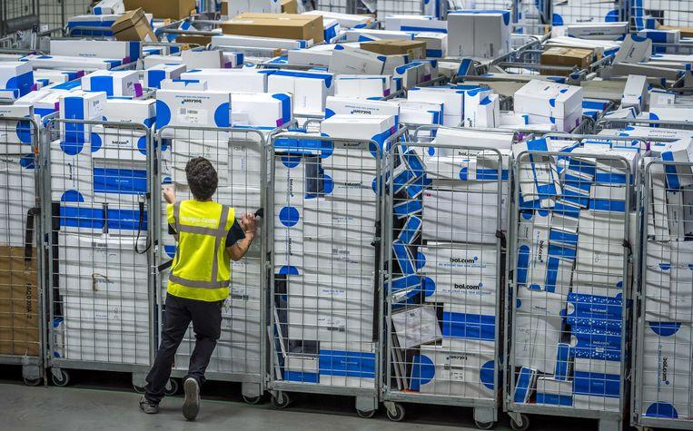 Pakjes worden voor verzending gesorteerd in het distributiecentrum van Bol.com tijdens de drukke dagen voor de viering van het sinterklaasfeest.  Beeld ANP, Lex van Lieshout