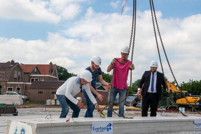 Vanaf links:de toekomstige bewoners Harm Bisschop en Klaas Visscher plaatsen samen met uitvoerder Gerrit Hofstede en wethouder Martijn Breukelman de laatste onderdelen van de vloer van Takenshof nummer 25. Foto Alex Mulder