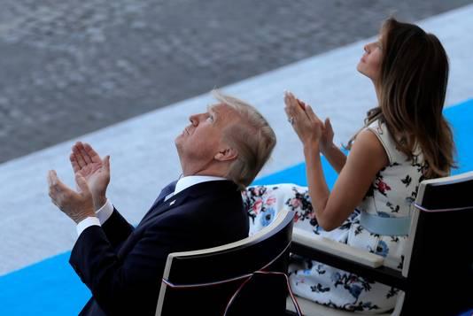 De Amerikaanse president en zijn first lady kijken naar overvliegende legertoestellen.