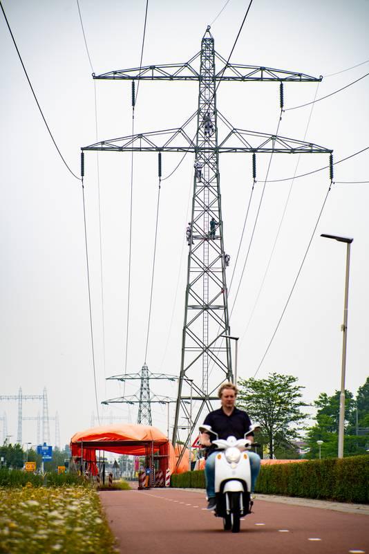 Om verkeer op het fietspad langs de Energieweg in Nijmegen te beschermen, is een tunnel van steigerpijpen met daarover een oranje zeil opgetrokken.
