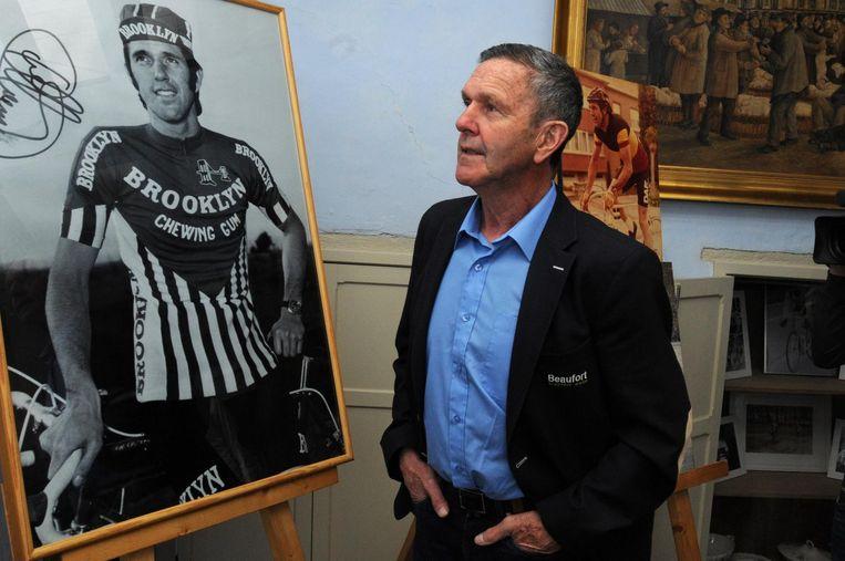 Roger De Vlaeminck kijkt aandachtig naar een portret van zichzelf op de expo